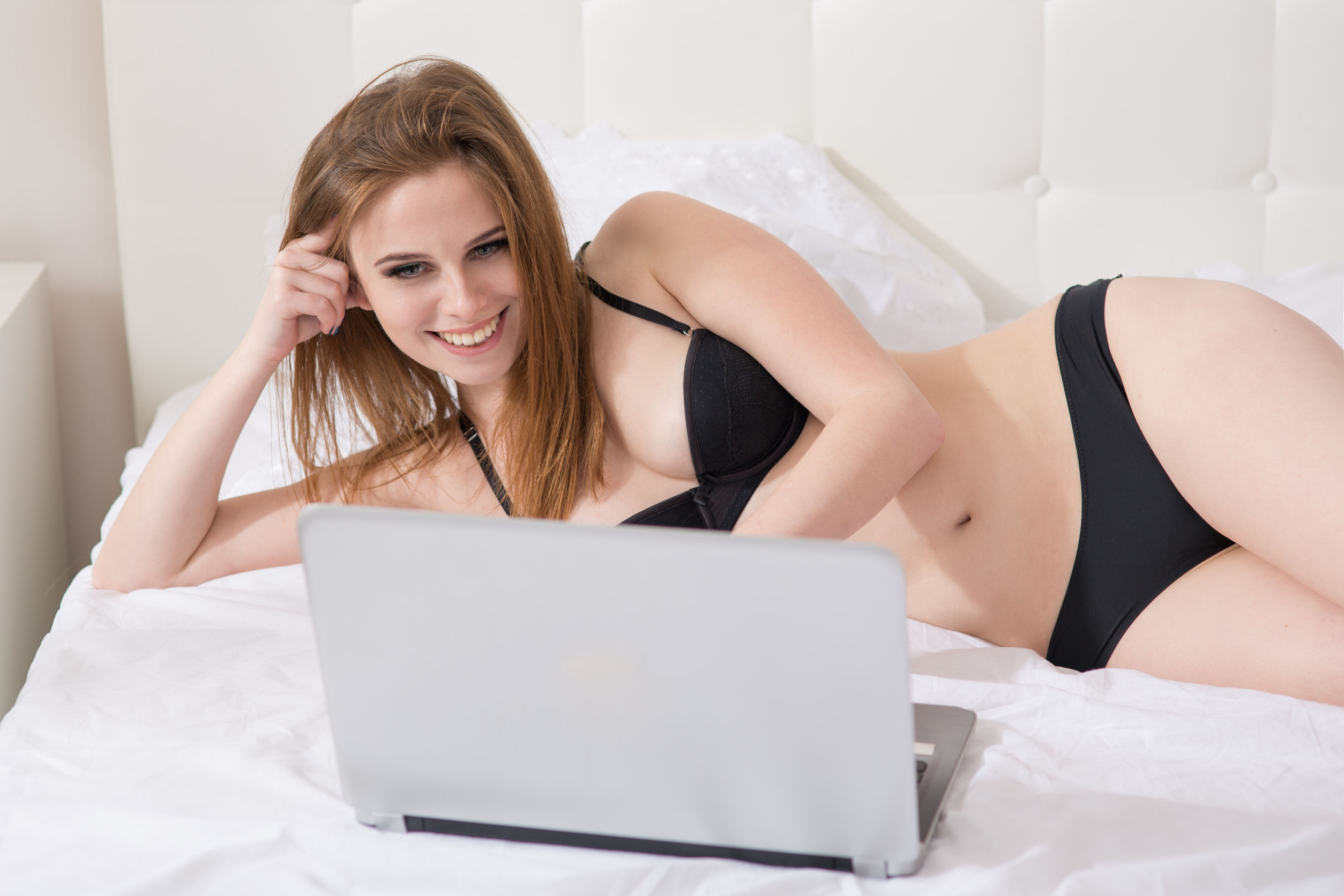 beautiful woman with a laptop on the bed cyber swinging